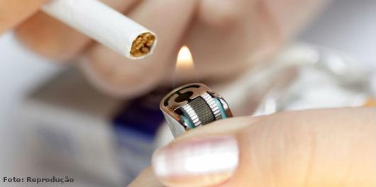 Foto de uma mulher acendendo um cigarro