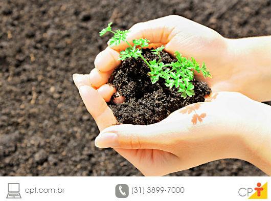 foto de mulher segurando um punhado de terra de boa qualidade (e com uma plantinha) nas mãos