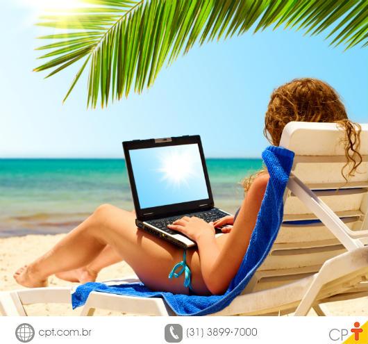 mulher na praia, passando férias, com notebook acessando a internet