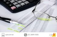 Planilha de despesas, calculadora e lápis.