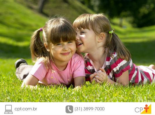 crianças felizes brincando deitadas na grama