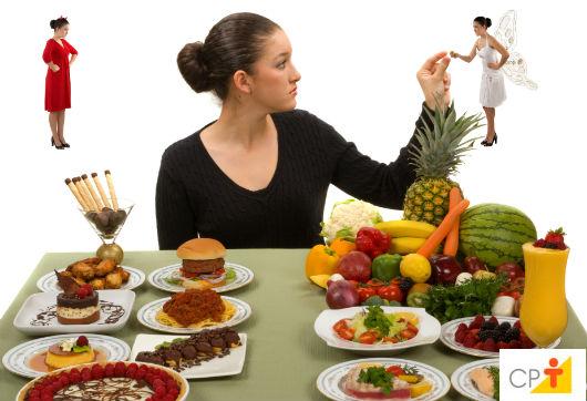 grávida escolhendo entre diferentes cardápios de alimentação: comidas saudáveis e não saudáveis