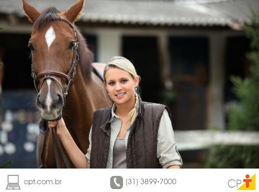 médica veterinaria segurando um cavalo pelas rédeas