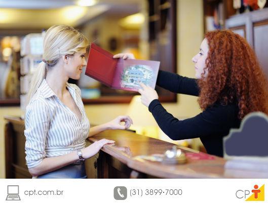 recepcionista de hotel prestando atendimento a uma cliente