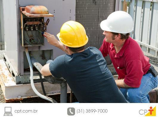 técnicos avaliando um aparelho de ar-condicionado